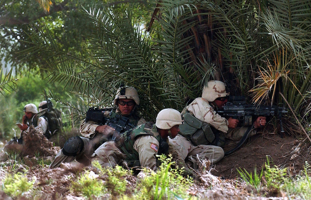 U.S. Army soldiers from the 1st Battalion 14th regiment  of the 25th Infantry Division take up cover positions after coming under fire April 16,2004 from militiamen loyal to controversial Iraqi Shia cleric Moqtada al-Sadr in Kufa, less than 10 miles outside the holy Iraqi city of Najaf.   ....