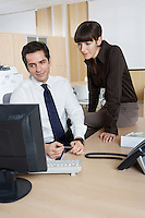 Business man and woman using computer at desk in office