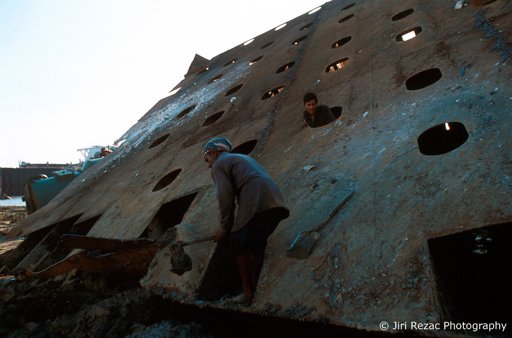 BANGLADESH CHITTAGONG MADHOM BIBIR HAT OCT00 - Labourers remove mud from inside a section of a decommissioned ship. Often the giant pieces of metal winched onto land contain large amounts of sticky mud which needs to me removed prior to dis-assembly...Several thousand labourers work on one medium-sized (50,000 ton) ship for a period of around three months, until it is completely dismantled and taken apart. ..Since Bangladesh does not possess mineral resources such as iron ore, it works out more cost-efficient to employ a large army of day-labourers to recycle the scrapped ships rather than to import ore. On average, a labourer can expect to earn a little more than 1 US Dollar per day...jre/Photo by Jiri Rezac..© Jiri Rezac 2000..Contact: +44 (0) 7050 110 417.Mobile: +44 (0) 7801 337 683.Office: +44 (0) 20 8968 9635..Email: jiri@jirirezac.com.Web: www.jirirezac.com..© All images Jiri Rezac 2000 - All rights reserved.