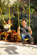 Five-year-old Kayla Morales  and host Brandon Johnson take a ride on the swings attached to the Snow White Playhouse, the center piece to the Village Square, in the Morales backyard. The village replaces a large slope and terracing that use to cause erosion in the backyard. As seen on HGTV's My House Goes Disney.