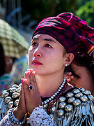 30 NOVEMBER 2017 - YANGON, MYANMAR: A woman in traditional dress, who was not able to get into the cathedral, prays on the street during the Papal Mass at St. Mary's Cathedral in Yangon. Thursday's mass was his last public appearance in Myanmar. From Myanmar the Pope went on to neighboring Bangladesh.    PHOTO BY JACK KURTZ
