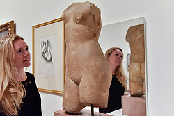 "© Licensed to London News Pictures. 01/08/2017. London, UK. A staff member views a 1st or 2nd century Roman ""Female torso"". Preview of ""Matisse in the Studio"", at the Royal Academy of Arts, Piccadilly, the first exhibition to consider how the personal collection of treasured objects of Henri Matisse were both subject matter and inspiration for his work.  Around 35 objects are displayed alongside 65 of Matisse's paintings, sculptures, drawings, prints and cut-outs.  The exhibition runs 5 August to 12 November 2017.  Photo credit : Stephen Chung/LNP"