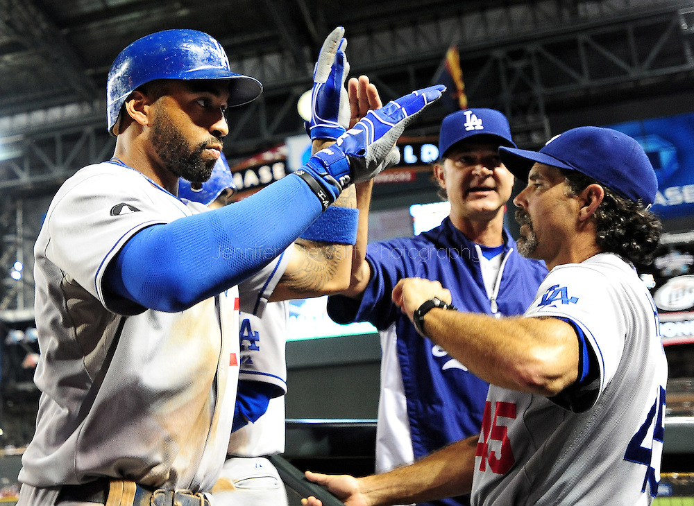 Sep. 27 2011; Phoenix, AZ, USA; Los Angeles Dodgers outfielder Matt Kemp (27) is congratulated by bench coach Trey Hillman (45) after scoring during the tenth inning against the Arizona Diamondbacks at Chase Field.  Mandatory Credit: Jennifer Stewart-US PRESSWIRE.