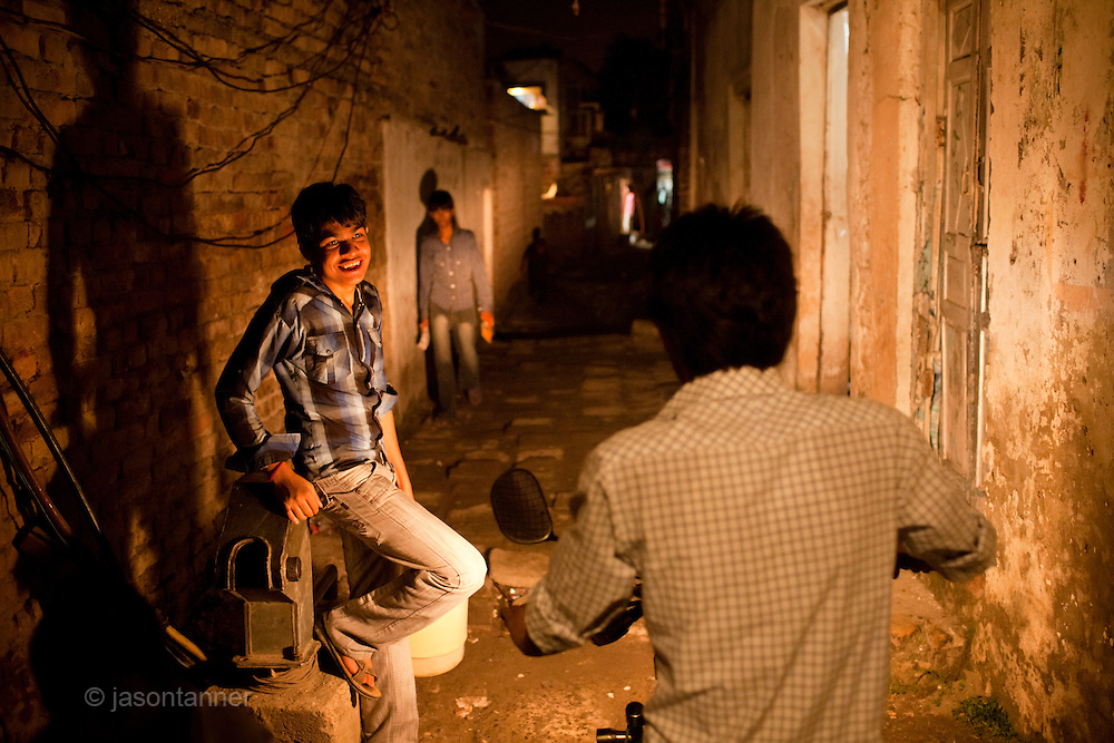 Islamabad: Young boys lit by motorcycle lights in the narrow alleyways of a Christian colony in Islamabad...Pakistan's Christian communities account for an estimated one percent of the country's 180 million population...I the middle of Islamabad's wealthiest neighbourhood is a 'colony' that's home to some 4000 Christians. Narrow alleys separate multi-storey, squalid houses with open sewers running meandering the alleys to the river that runs through the heart of the colony...Some are recent arrivals from Faisalabad and Gojra, where recent sectarian killings forced many to relocate to the relative safety of the capitol territory. Many are second and third generation residents squatting on land that sees no development assistance from the Capital Development Authority. Power outages are frequent, many residents sleep on the roofs during the long summer months, there are no air-conditioners in the colony...Many of the residents are unemployed; those fortunate to have any income usually work as servants, gardeners, drivers, security guards or cleaners. ..Discrimination against the Christian minorities is rampant in Pakistani society. Many suspect the government of deliberately keeping them at the bottom of the economic ladder to appease the radical religious parties...©JTanner/August2011