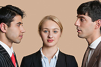 Portrait of a young businesswoman with male colleagues staring at each other over colored background