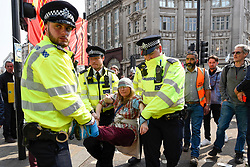 "© Licensed to London News Pictures. 17/04/2019. LONDON, UK.  Police officers arrest a protester, who is wearing a Thresa May face mask, at Oxford Circus during ""London: International Rebellion"", on day three of a protest organised by Extinction Rebellion, demanding that governments take action against climate change.  Marble Arch, Oxford Circus, Piccadilly Circus, Waterloo Bridge and Parliament Square have been blocked by activists in the last three days.  Police have issued a section 14 order requiring protesters to convene at Marble Arch only so that the protest can continue.  Photo credit: Stephen Chung/LNP"
