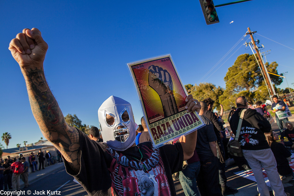 """20 MARCH 2012 - PHOENIX, AZ: A demonstrator dresses in """"Lucha Libre"""" (Mexican wrestling) mask during a student protest in support of the DREAM Act on 75th Ave in front of Trevor G. Browne High School Tuesday.  PHOTO BY JACK KURTZ"""