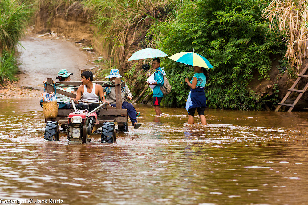 """21 MAY 2013 - MAE KU, TAK, THAILAND:  Burmese patients from the Mawker Thai SMRU clinic in Mae Ku, Thailand walk across the Moie River back to Burma, while a """"bus"""" brings more patients across the river into Thailand. Health professionals are seeing increasing evidence of malaria resistant to artemisinin coming out of the jungles of Southeast Asia. Artemisinin has been the first choice for battling malaria in Southeast Asia for 20 years. In recent years though,  health care workers in Cambodia and Myanmar (Burma) are seeing signs that the malaria parasite is becoming resistant to artemisinin. Scientists who study malaria are concerned that history could repeat itself because chloroquine, an effective malaria treatment until the 1990s, first lost its effectiveness in Cambodia and Burma before spreading to Africa, which led to a spike in deaths there. Doctors at the Shaklo Malaria Research Unit (SMRU), which studies malaria along the Thai Burma border, are worried that artemisinin resistance is growing at a rapid pace. Dr. Aung Pyae Phyo, a Burmese physician at a SMRU clinic just a few meters from the Burmese border, said that in 2009, 90 percent of patients were cured with artemisinin, but in 2010, it dropped to about 70 percent and is now between 55 and 60 percent. He said the concern is that as it becomes more difficult to clear the parasite from a patient, progress that has been made in combating malaria will be lost and the disease could make a comeback in Southeast Asia.  PHOTO BY JACK KURTZ"""