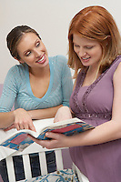 Two women looking at book by cradle