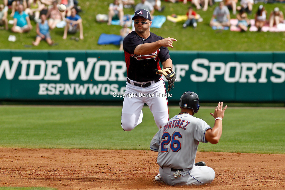 March 5, 2011; Lake Buena Vista, FL, USA; Atlanta Braves second baseman Dan Uggla (26) forces out New York Mets right fielder Fernando Martinez (26) and throws to complete a double play during a spring training exhibition game at Disney Wide World of Sports complex.  Mandatory Credit: Derick E. Hingle