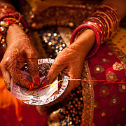 An Indian bride holds a thread and a fifty rupee note during a Hindu wedding in Delhi. The other side of the thread is held by the groom on her left. As a part of the ceremony, they will later stretch the thread until it tears.