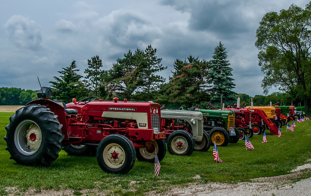 A display of classic tractors with brands such as International, Ford, Oliver, John Deere, Chalmers and more.  This photo was taken in Wisconsin.
