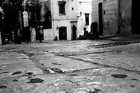 Scorcio di via Cattedrale, semideserta per lo svolgimento della partita di calcio della Nazionale italiana durante i mondiali del 2010. Si intravede inlontananza un gruppetto di pesone sedute sul marciapiede di fronte ad un negozio di souvenir intente a guardare la partita da un televisore piccolo sistemato all'ingresso del negozio.