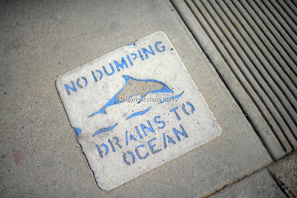 No Dumping, Drains to Ocean sign on sidewalk, Los Angeles, California.