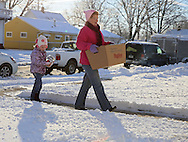 Grace Bruns (from left), 5, of Fairfax and Sue Berger of Cedar Rapids deliver a food box to a house in Southwest Cedar Rapids as the Society of St. Vincent de Paul delivers 237 holiday meals to families in Cedar Rapids, Marion, and Hiawatha on Saturday morning, December 22, 2012. (Stephen Mally/Freelance)