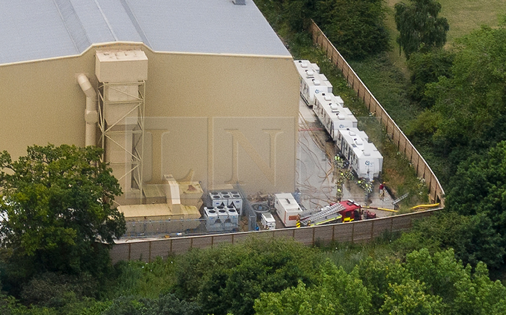 © Licensed to London News Pictures. 11/07/2019. Watford, UK. Fire engines can be seen at the back of Stage P at the Warner Bros film studios at Leavesden near Watford as they deal with the aftermath of a blaze that started overnight. Fire officers at to cut a large hole in the surrounding fence (R) to run their hoses in to the seat of the fire. The fire service were called in overnight after a fire started in one of the studios. The Harry Potter series was filmed here. Photo credit: Peter Macdiarmid/LNP