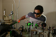 A graduate student works in a physics lab in the Science Research Lab located between Smith and Williams Hall.