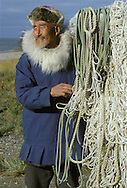 Eskimo man mends fish nets in Kotzebuw