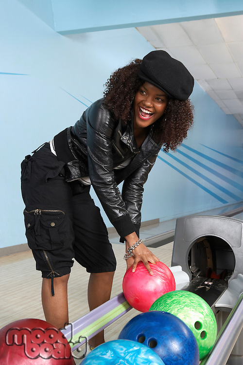 Young Woman Selecting Bowling Ball