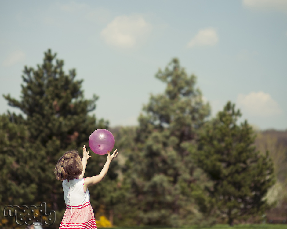 Young girl catching purple ball in park