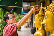 """12 NOVEMBER 2012 - BANGKOK, THAILAND:   A man paints a statue of the Buddha in front of his shop on Bamrung Muang Street in Bangkok. Thanon Bamrung Muang (Thanon is Thai for Road or Street) is Bangkok's """"Street of Many Buddhas."""" Like many ancient cities, Bangkok was once a city of artisan's neighborhoods and Bamrung Muang Road, near Bangkok's present day city hall, was once the street where all the country's Buddha statues were made. Now they made in factories on the edge of Bangkok, but Bamrung Muang Road is still where the statues are sold. Once an elephant trail, it was one of the first streets paved in Bangkok. It is the largest center of Buddhist supplies in Thailand. Not just statues but also monk's robes, candles, alms bowls, and pre-configured alms baskets are for sale along both sides of the street.    PHOTO BY JACK KURTZ"""
