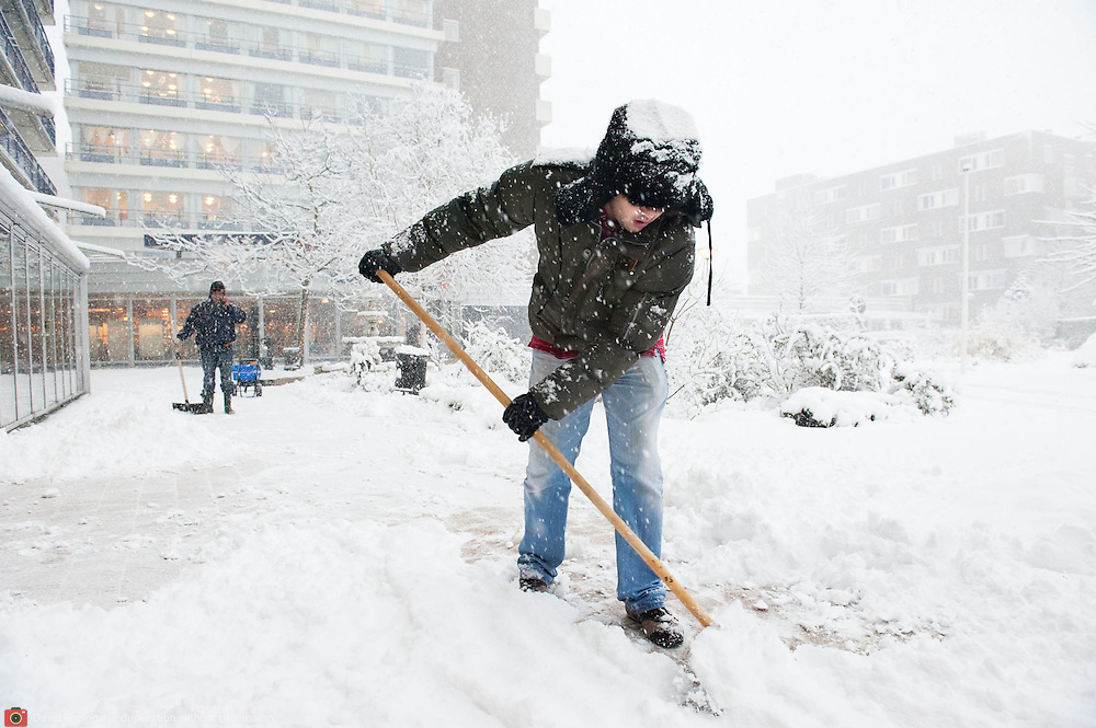 Nederland, Rotterdam, 17 december 2010. Weeralarm, zware sneeuwval in de Randstad. Medewerkers van bejaardentehuis Humanitas, gekleed in dikke winterkleding en mutsen, maken het trottoir naar de ingang van het ouderenhuis vrij van sneeuw. Wegscheppen van sneeuw, pad maken in de sneeuw. Foto: David Rozing