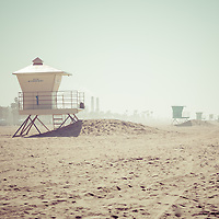 Huntington Beach Lifeguard Tower #1 retro photo with more lifeguard towers in the background. Photo has 1950's / 1960's nostalgic tone applied. Huntington Beach is a seaside beach city in Orange County California and is also known as Surf City USA. Image Copyright © Paul Velgos All Rights Reserved.