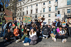 London, UK. 15th February, 2019. Students block a road around Parliament Square during the YouthStrike4Climate for Climate Day which was attended by thousands of young people. Strike events involving schools all over the UK were organised by UK Student Climate Network and the UK Youth Climate Coalition to demand that the Government declare a climate emergency and take positive steps to address the climate crisis, including highlighting the issue as part of the school curriculum, as well as lowering the voting age to 16.