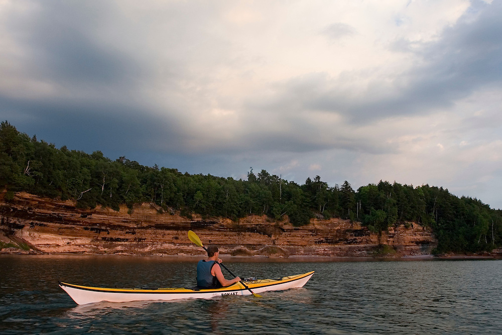 A sea kayaker paddles by sandstone cliffs at dusk at Grand Island National Recreation Area in Munising Michigan.