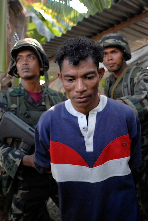 Malaysian troops detain a suspected gang member after a clash between rival gangs near the bridge at Comora, Dili. East Timor 04/06/06