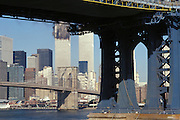 September 11 2001 World Trade Center on fire with the Manhattan Bridge pillars in the foreground.