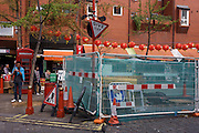 Roadworks and construction fencing in London's Chinatown with paper lanterns hanging in background before Moon Festival.