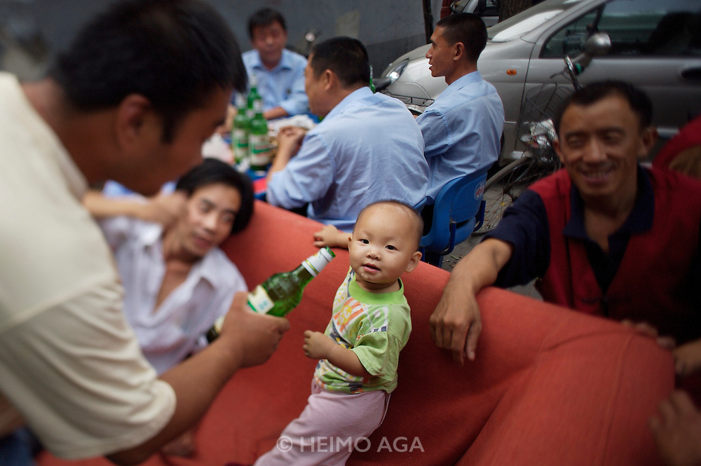 A typical Hutong (old style district). Men feeding a baby boy with beer.