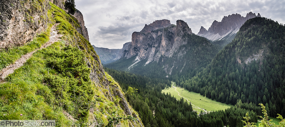 A short ascent to Wolkenstein Castle gives a good view over Vallunga/Langental valley, in Puez-Geisler Nature Park, Val Gardena, Dolomites, South Tyrol, Italy, Europe. The beautiful ski resort of Selva di Val Gardena (German: Wolkenstein in Gröden; Ladin: Sëlva Gherdëine) makes a great hiking base in the Dolomites, in the South Tyrol region (Trentino-Alto Adige/Südtirol) of Italy, Europe. For our favorite hike in the Dolomiti, start from Selva with the first morning bus to Ortisei, take the Seceda lift, admire great views up at the cross on the edge of Val di Funes (Villnöss), then walk 12 miles (2000 feet up, 5000 feet down) via the steep pass Furcela Forces De Sieles (Forcella Forces de Sielles) to beautiful Vallunga (trail #2 to 16), finishing where you started in Selva. The hike traverses the Geisler/Odle and Puez Groups from verdant pastures to alpine wonders, all preserved in a vast Nature Park: Parco Naturale Puez-Odle (German: Naturpark Puez-Geisler; Ladin: Parch Natural Pöz-Odles). UNESCO honored the Dolomites as a natural World Heritage Site in 2009. This panorama was stitched from 2 overlapping photos.