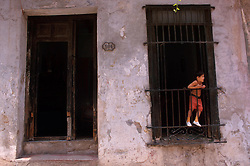 A young boy passes time looking out the window of his family's home in Havana, Cuba. (Photo © Jock Fistick)