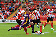 Alex Simmons brings down Jack Barthram during the Vanarama National League match between Lincoln City and Cheltenham Town at Sincil Bank, Lincoln, United Kingdom on 8 August 2015. Photo by Antony Thompson.
