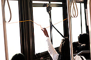 A woman pulls a string to notify a CTRAN bus driver of wanting to get out at a stop March 31, 2010 marked Clayton County, Georgia's last day of the county's public bus system, CTRAN, running.