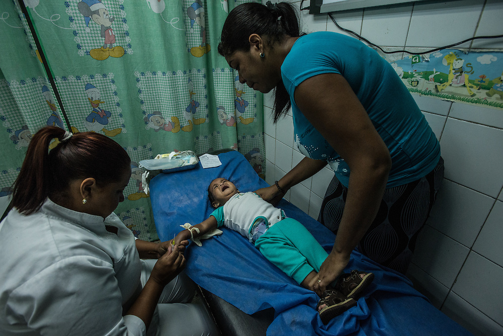 CATIA LA MAR, VENEZUELA - APRIL 12, 2016: Lere Briceño holds down her 11-month old daughter, LoreAlex  in the pediatric emergency room of a government-run clinic in Catia La Mar. Doctors here say they regularly have to turn patients away, because they don't have the majority of medicines  or medical equipment and supplies needed to give them medical attention.  When they do accept patients, they have to work with extremely limited resources. They said they regularly run out of medicines and supplies such as IV fluids, high-blood pressure medicine, baby asprin and masks. Despite having the largest oil reserves in the world, falling oil prices and wide-spread government corruption have pushed Venezuela into an economic crisis, with the highest inflation in the world and chronic shortages of food and medical supplies.   PHOTO: Meridith Kohut for The New York Times