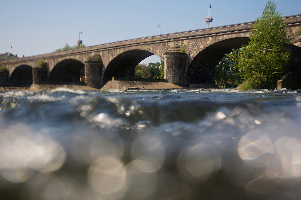 Split-level view of the currents and the old stone bridge of Pont-du-Chateau, Auvergne, France.