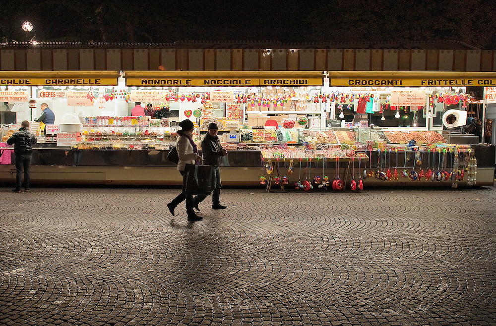 VERONA, ITALY - DECEMBER 04: Two people walk in front of a large swet shop at the Verona Christmas Market on December 4, 2010 in Verona, Italy. Christmas markets, fairs, lights and nativity scenes fill Northern Italian cities and villages from December through January 6.