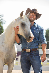 hot cowboy enjoying time with a horse on a ranch