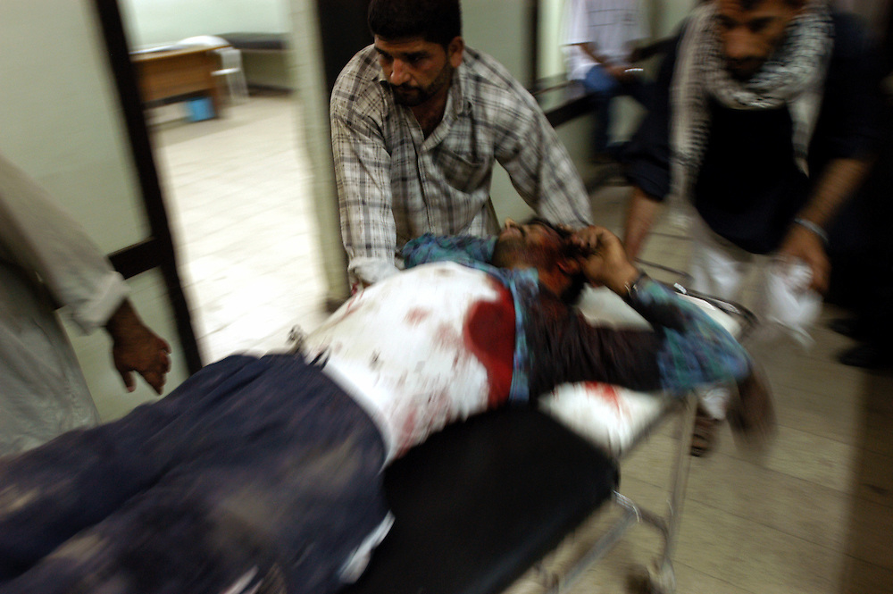 A man with multiple gunshot wounds is wheeled into the emergency room at the al-Kadisia hospital in Thora City, formerly known as Saddam City. The neighborhood is a vast slum of 3 million Shiite Muslims, long oppressed and marginalized by Saddam's regime. The area is a hotbed for the insecurity and violence that has thrived with the absence of authority in the country..Baghdad, Iraq. 06 May 2003..Photo © J.B. Russell