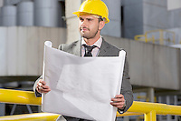 Young businessman holding blueprint while looking away at construction site