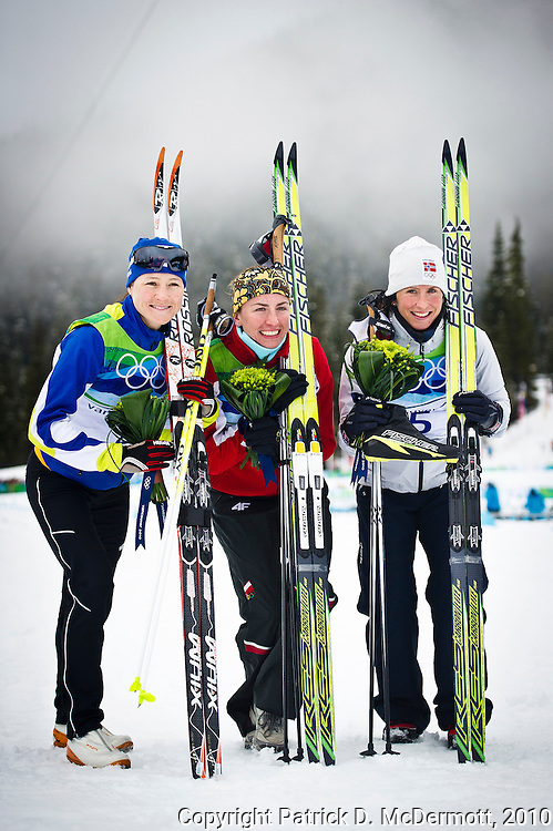 (L-R) Aino-Kaisa Saarinen of Finland celebrates winning bronze, Justyna Kowalczyk of Poland gold and Marit Bjoergen of Norway silver in the ladies' 30 km mass start cross-country skiing classic on day 16 of the 2010 Vancouver Winter Olympics at Whistler Olympic Park Cross-Country Stadium on February 27, 2010 in Whistler, Canada.