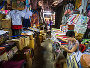 29 SEPTEMBER 2015 - BANGKOK, THAILAND:  A woman reads a Bangkok newspaper in a market near Saphan Lek. Street vendors and illegal market vendors in the Saphan Lek area will be removed in the next two weeks as a part of an urban renewal project coordinated by the Bangkok Metropolitan Administration. About 500 vendors along Damrongsathit Bridge, popularly known as Saphan Lek, have 15 days to relocate. Vendors who don't move will be evicted. Saphan Lek is just one of several markets and street vending areas being closed in Bangkok this year. The market is known for toy and replica guns, bootleg and pirated DVDs and CDs and electronic toys.   PHOTO BY JACK KURTZ