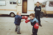 Two little toddlers boxing on Winterbourne Travellers site, Bristol, UK, 1990's