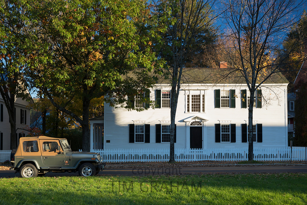 Typical stylish and elegant white clapboard New England dwelling house with white paling fence and Jeep automobile at Woodstock, Vermont, USA