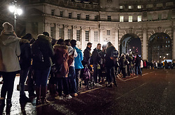 © Licensed to London News Pictures. 31/12/2017. London, UK. Ticket holders line up in the Mall before entering the secure area on the banks of the River Thames to watch the New Years Eve fireworks at midnight.  Photo credit: Peter Macdiarmid/LNP
