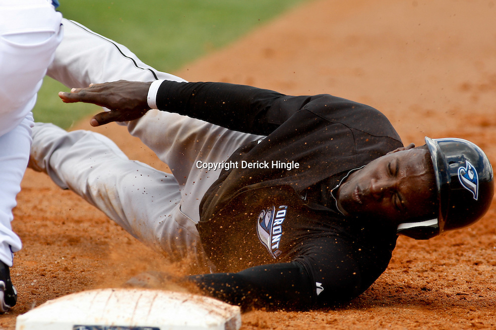 March 8, 2011; Port Charlotte, FL, USA; Toronto Blue Jays shortstop Adeiny Hechavarria (3) dives back to first base on an attempted pick off play during a spring training exhibition game against the Tampa Bay Rays at Charlotte Sports Park.  Mandatory Credit: Derick E. Hingle-US PRESSWIRE