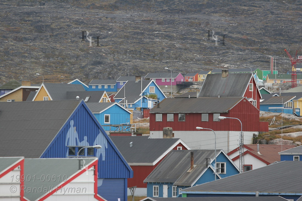 Colorfully painted homes and buildings brighten the bare, rocky slopes of Ilulissat, third largest town in Greenland.